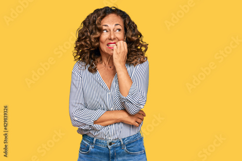 Middle age hispanic woman wearing casual clothes looking stressed and nervous with hands on mouth biting nails Fototapeta