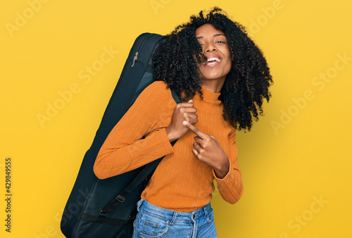 Fotografie, Obraz Young african american girl wearing guitar case smiling happy pointing with hand