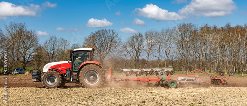 Obraz na plátně Tractor with plough and roundabout harrow cultivating the soil in the field | C