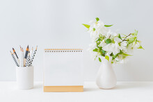 Mockup White Desk Calendar And With Spring Flowers In A Vase On A Light Background