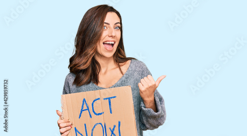 Fotografiet Young brunette woman holding act now banner pointing thumb up to the side smilin