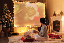 MYKOLAIV, UKRAINE - DECEMBER 24, 2020: Woman Watching The Grinch Movie Via Video Projector In Room. Cozy Winter Holidays Atmosphere