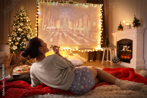 Obraz MYKOLAIV, UKRAINE - DECEMBER 24, 2020: Woman watching Harry Potter and Philosopher's Stone movie via video projector in room. Cozy winter holidays atmosphere - fototapety do salonu