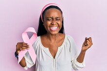 Young African Woman Holding Pink Cancer Ribbon Screaming Proud, Celebrating Victory And Success Very Excited With Raised Arm