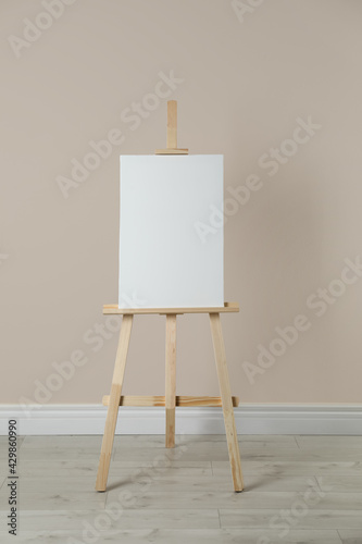 Canvas Print Wooden easel with blank canvas near beige wall