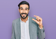 Young Hispanic Man Wearing Business Clothes Smiling And Confident Gesturing With Hand Doing Small Size Sign With Fingers Looking And The Camera. Measure Concept.