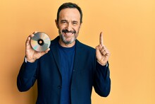 Middle Age Hispanic Man Holding Compact Disc Smiling With An Idea Or Question Pointing Finger With Happy Face, Number One