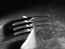 Closeup Shot Of Two Metal Forks On A Black Fabric