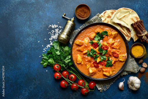 Fototapeta Chicken tikka masala - traditional dish of indian cuisine in a black bowl.Top view with copy space. obraz