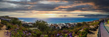 A Stunning Shot Of The Vast Blue Ocean Water And A Hillside Filled With Homes And Lush Green Plants And Flowers And A Footpath With People Walking And Clouds At Dana Strands Beach In Dana Point CA