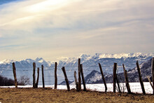 Beautiful Snow-capped Mountains With A Barbed Wire Fence In The Foreground