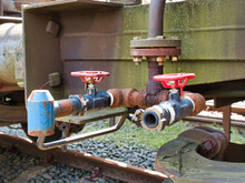 Closeup Of Two Red Valves On A Rusty Pipe With A Train Wagon And Railway In The Background