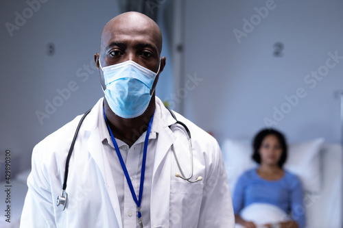 Portrait of african american male doctor in hospital wearing face mask, female patient in bed