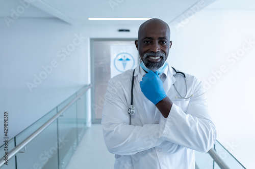 Photo Portrait of smiling african american male doctor in hospital corridor holding fa