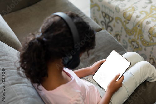 Elevated view of mixed race girl wearing wireless headphones sitting on couch using digital tablet