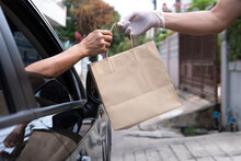 Woman Driver Hand Received Shopping Brown Paper Bag Out Of Black Car Open Window Driving Thru Pickup From Seller Wearing Glove At Asian Home Meeting Social Distancing Requirements Supporting Business