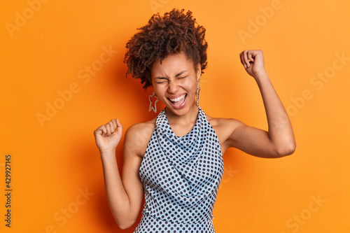Isolated shot of beautiful African American woman has fun laughs from joy dresse Fototapeta