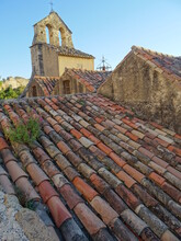Red Tile Roof Of A House And Old Stone Church In A Village In The South Of France