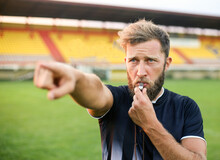 A Handsome Football Referee With A Beard Plays The Whistle