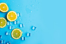 Juicy Fresh Yellow Lemon Slices And Ice Cubes On A Blue Background. Top View, Flat Lay