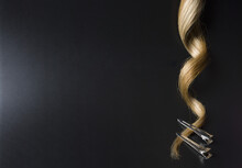 Strand Of Blond Curly Hair With Clips On The Edges On A Black Background,  Objects Vertical Placement, Spotted With Lights