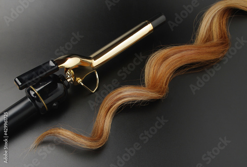 Valokuva Professional Hairdressing Curling Iron With A lock Of Waved Hair on A Black Back