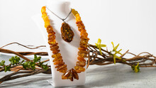 Orange Sparkling Baltic Amber Necklace And Green-yellow  Amber Pendant Displayed On A White Jewelry Stand On A Gray Surface.  Isolated Amber Jewelry.  Retro Composition.