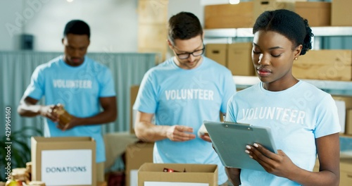 Foto Portrait of beautiful young concentrated African American woman volunteer standing in charity organization warehouse writing and checking donations