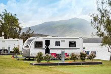 RV Caravan Camping At The Caravan Park On The Lake With Mountains On The Horizon. Camping Vacation Travel Concept