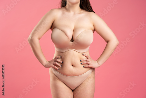 Fat woman with large breasts in a push-up bra on pink background, overweight female body - fototapety na wymiar