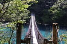 寸又峡、春の風景。南アルプス大井川上流に流れ込む寸又川が造る渓谷。エメラルドグリーンの水がゆっくり流れ幻想的な風景が見られる。流れをせき止めた大間ダム(チンダル湖)付近には吊り橋がかけられ、「夢の吊り橋」として観光名所となっている。