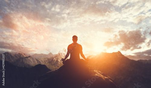 Foto Man in yoga pose, zen meditation at sunset.