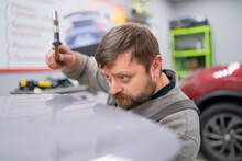 Close Shot Of Dent Removing Without Paint, Bearded Professional Worker Makes Accurate Blow Rubber Hammer