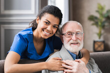Friendly Mature General Practitioner Communicating With Pleasant 80s Male Patient, Sitting Together On Sofa. Smiling Trustful Young Doctor Giving Psychological Help To Elder Man At Home Visit.