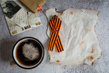 """St. George Ribbon, Cap, Coffee Mug And Burnt Paper On The Background Of Concrete. The Inscription In Russian: """"The Great Victory On May 9"""". Defender Of The Fatherland Day. Top View, Copy Space."""