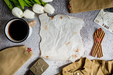 The Holiday Is May 9. A St. George Ribbon, A Coffee Mug, Tulips And Burnt Note Paper On A Concrete Background. The Concept Of The Great Victory. Top View, Copy Space For Text.