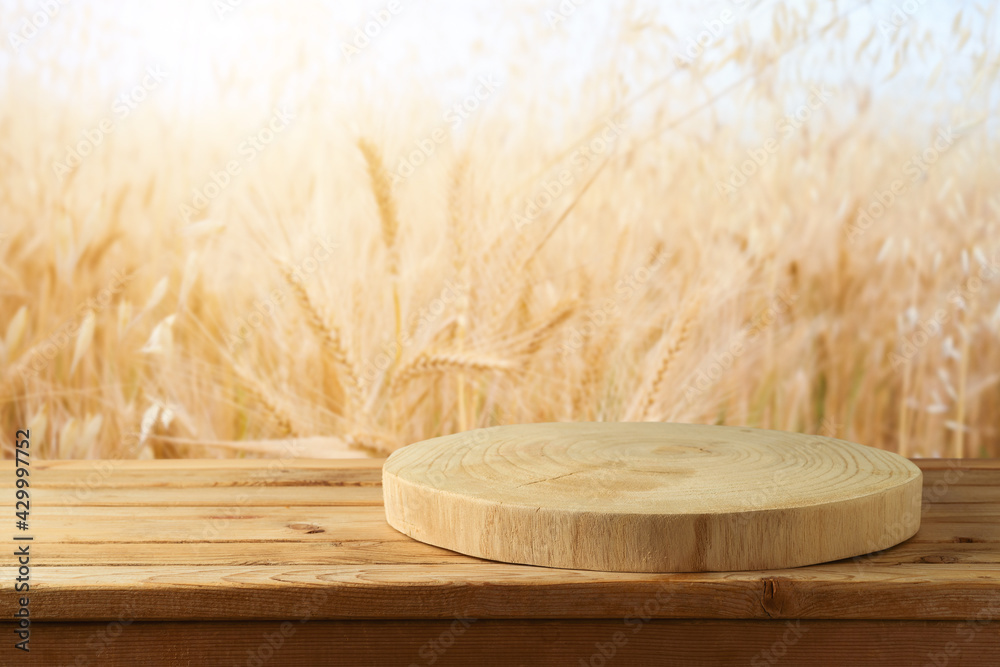Obraz Empty wooden log on rustic table over wheat field background.  Jewish holiday Shavuot mock up for design and product display. fototapeta, plakat