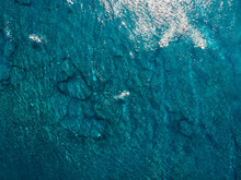 Aerial View Of Surfers In Tropical Blue Ocean With Waves At Bali. Top View