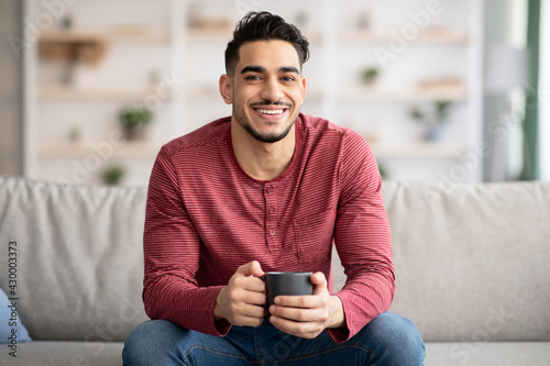 Canvas Print Relaxed arab guy sitting on couch and drinking tea