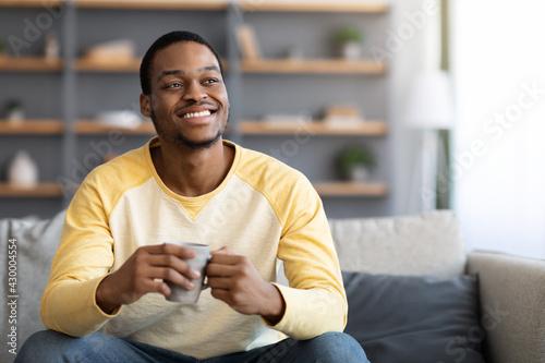 Fototapeta Relaxed handsome black man drinking coffee in living room obraz