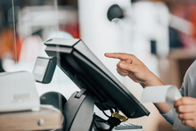 Young Saleswoman Doing Process Payment On The Touchscreen POS, Counting Sale In The Cash Register, Finance Concept