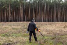 Treasure Hunter. Man With Metal Detector In The Field