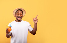 Amazing Offer. Excited African American Man With Yummy Summer Cocktail Pointing At Blank Space On Yellow Background
