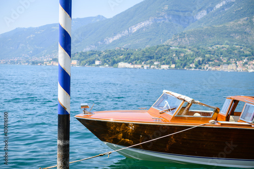 Vintage wooden motorboat parked by venetian pole on shore of the lake light refl Fototapeta