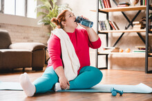 Tired After Hard Physical Training Caucasian Fat Young Woman Thirsty Relaxing On The Mat. Chubby Plus Size Woman Doing Fitness For Being In Good Shape And Lose Weight