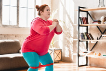 Fat Plus Size Obese Woman Doing Sit-ups With Fitness Rubber Band At Home Fot Burning Calories And Losing Weight. Plump Woman Exercising Indoors For Being In Good Shape