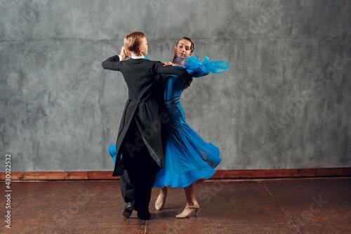 Fototapeta Young man and woman dancing waltz at ballroom.