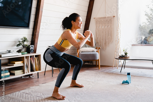 Sporty young african woman exercising at home Poster Mural XXL