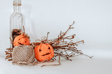 Halloween Pumpkin Embroideries, Tree Branches, A Jute Twine, And A Bottle With Nuts