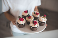 Woman Bake Cup Cake With Whipped Crem Icing And Flower Decoration In Kitchen At Home Close Up. Celebration.